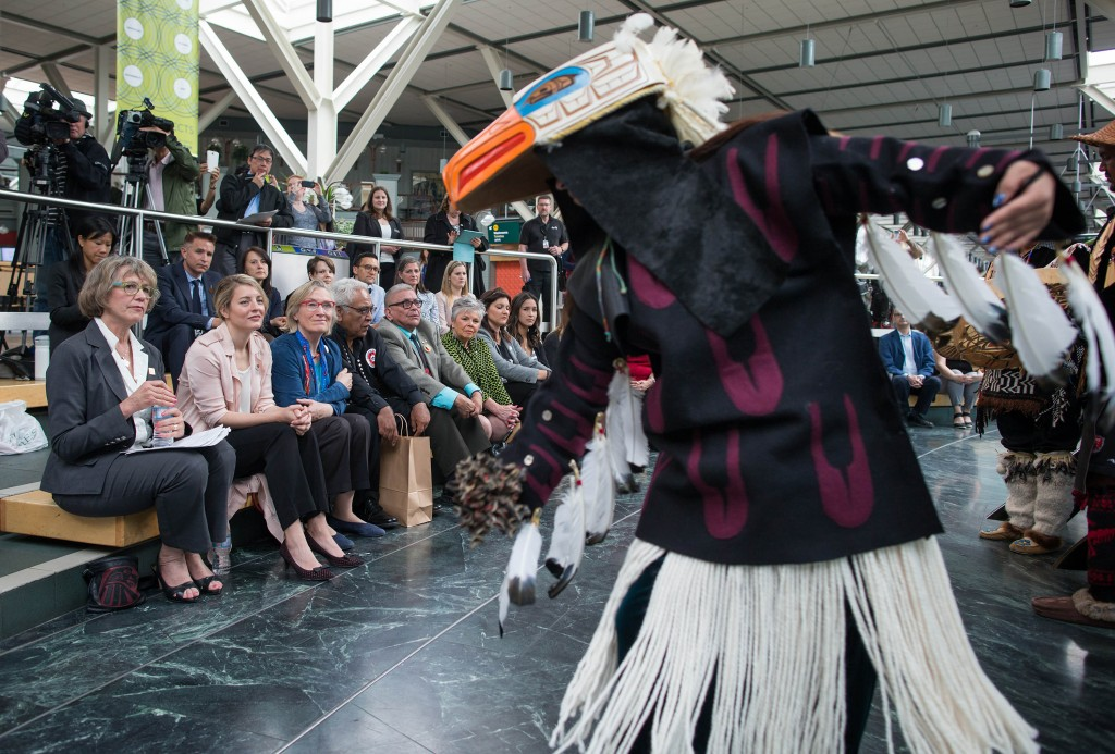 Vancouver Quadra MP Joyce Murray, from left to right, Melanie Joly, Minister of Canadian Heritage and Carolyn Bennett, Minister of Indigenous and Northern Affairs Canada, watch as a member of the Eagle Song Dancers performs during a Canada 150 announcement at Vancouver International Airport in Richmond, B.C., on Tuesday May 24, 2016. The Canadian Press Images PHOTO